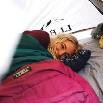 smiling woman in sleeping bag in a tent
