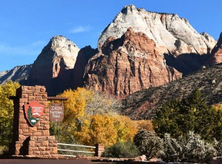 A beautiful rock formation against a bright blue sky with a Zion National Park entrance sign in the foreground.