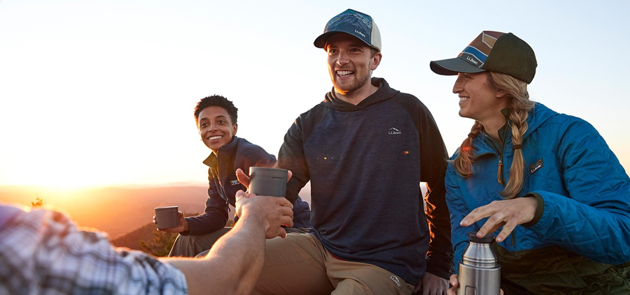 Friends drinking hot tea on top of a mountain as the sun begins to set.
