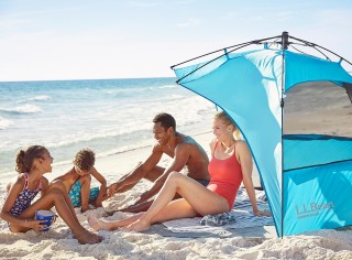 Family of 4 sitting in and around a sun shelter on the beach.