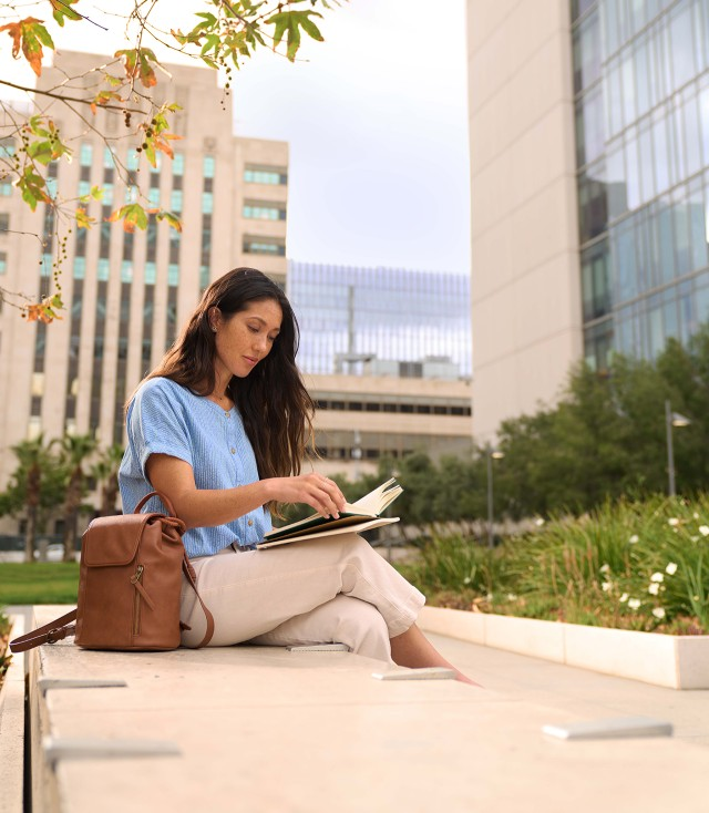 Woman sitting on a bench in the city reading a book.