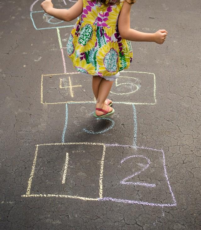 A child playing hopscotch on pavement.