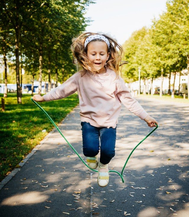 A young girl jumping rope.