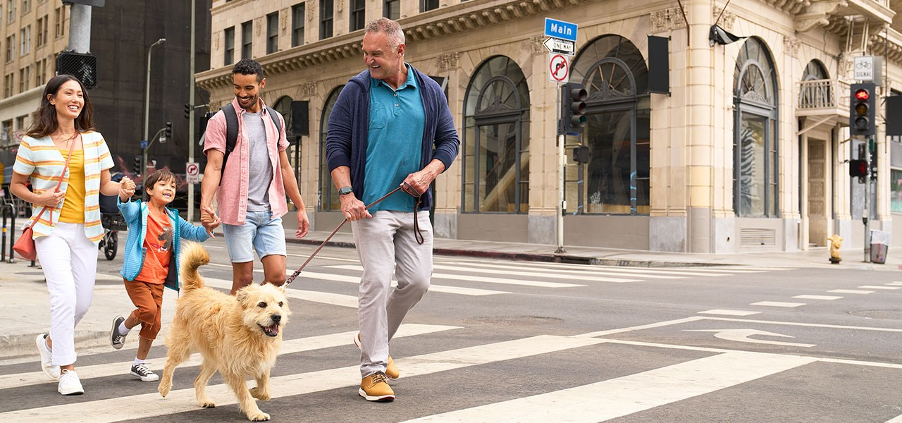 Family of four walking their dog in the city.
