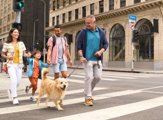 Family of 4 crossing the street in the city with their dog.