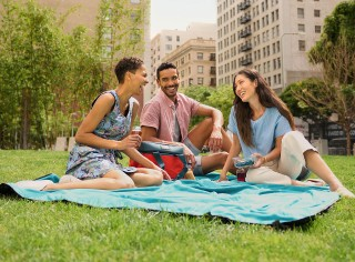 3 friends sitting on a blanket on the grass having a picnic in the city.