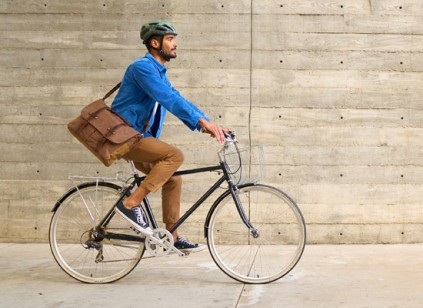 A man riding a bike in the city carrying a messenger bag.