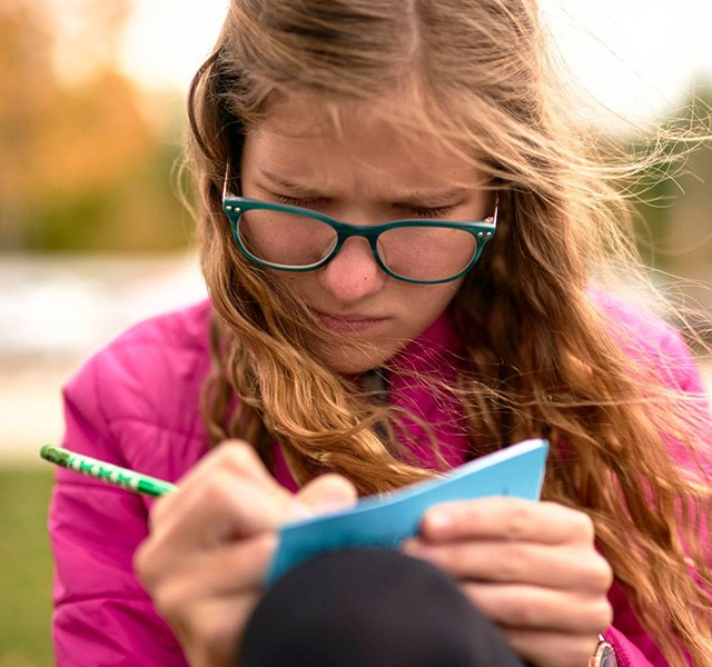 Girl recording weather in notebook