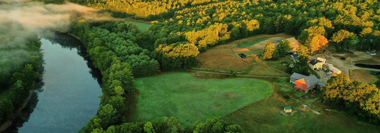 An aerial view of a beautiful farm along a river.