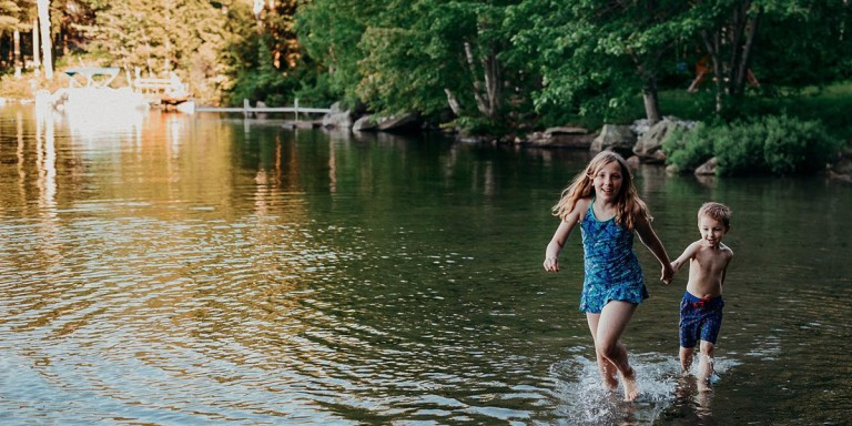 Two kids holding hands, walking through shallow water.