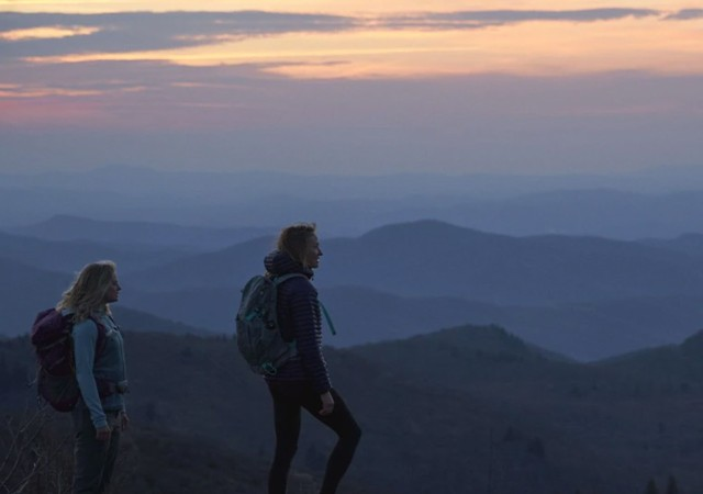 Two figures with backpacks silhouetted against receding blue mountains at twilight.