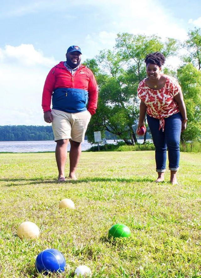 A couple playing bocce ball by the water.