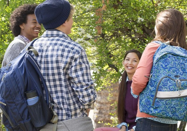 Four smiling students with backpacks gathered outside.