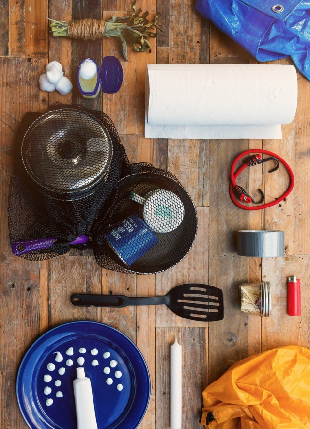 An overhead view of a wooden table on which various camping accessories are gathered.