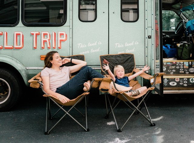 Madison and Margie Bowman in front of the family's converted shuttle bus, Buster.