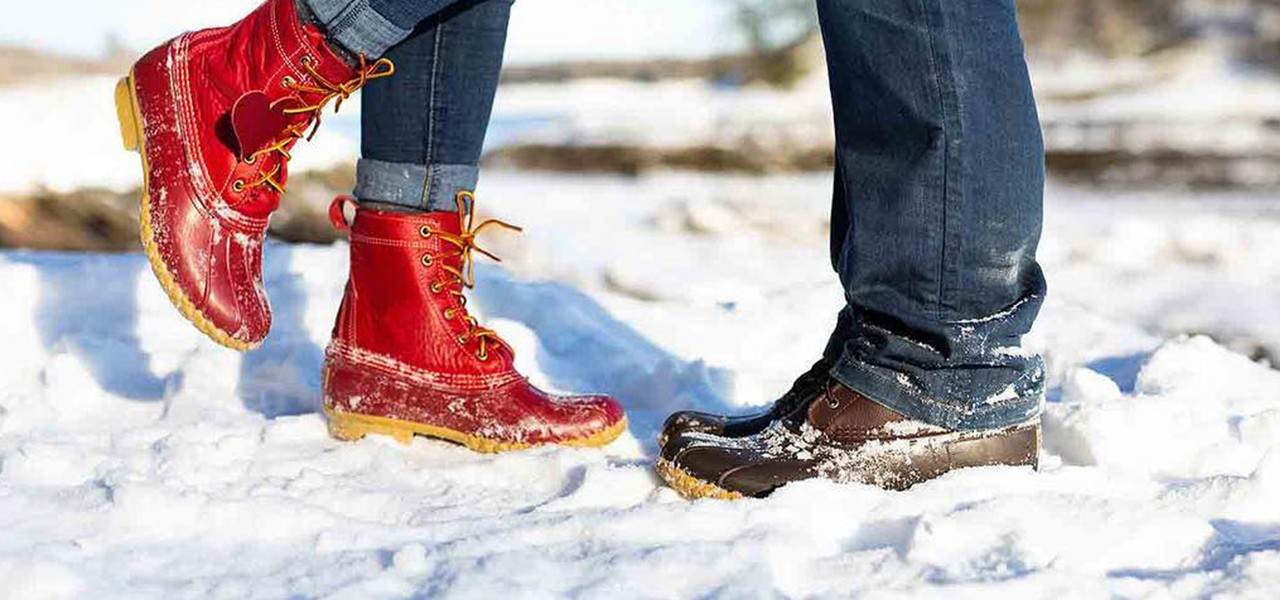 Two sets of Bean Boot clad feet facing each other in the snow, one red Bean Boot raised as if they are kissing.
