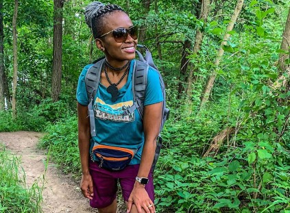 Dineo Dowd hiking on a forest trail.