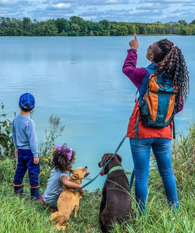 Dineo Dowd wearing backpack with 2 children and 2 dogs at water's edge, enjoying the view.
