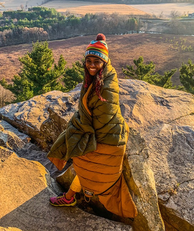 Dineo Dowd sitting on a rock wrapped up in a sleeping bag.
