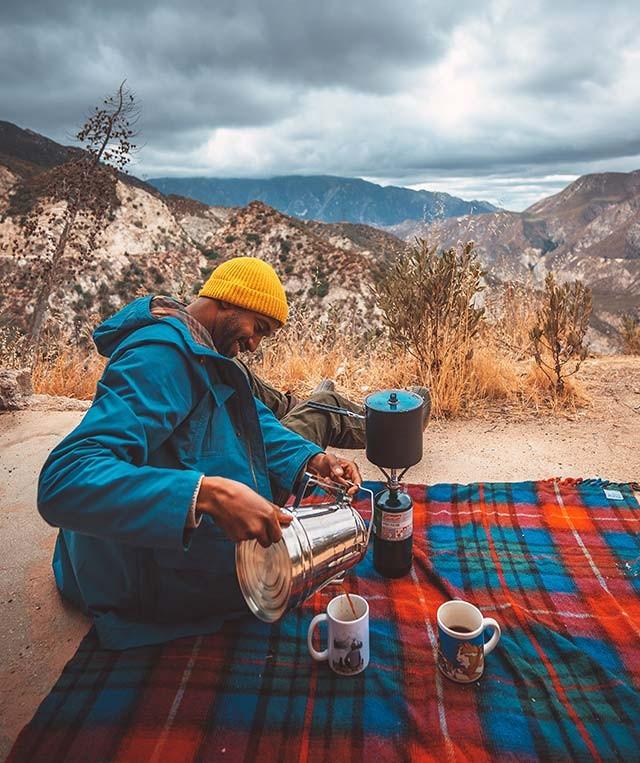 Joshua Walker sitting on a blanket in a beautiful mountain setting making coffee.