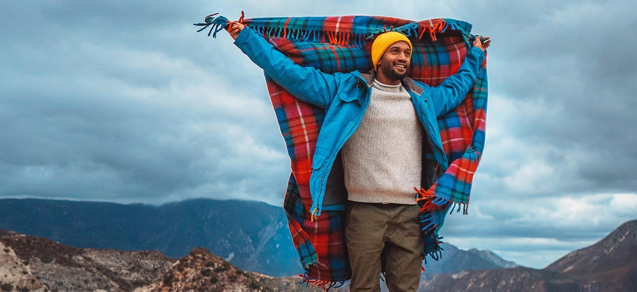 Joshua Walker holding up a fluttering plaid blanket, mountains all around.