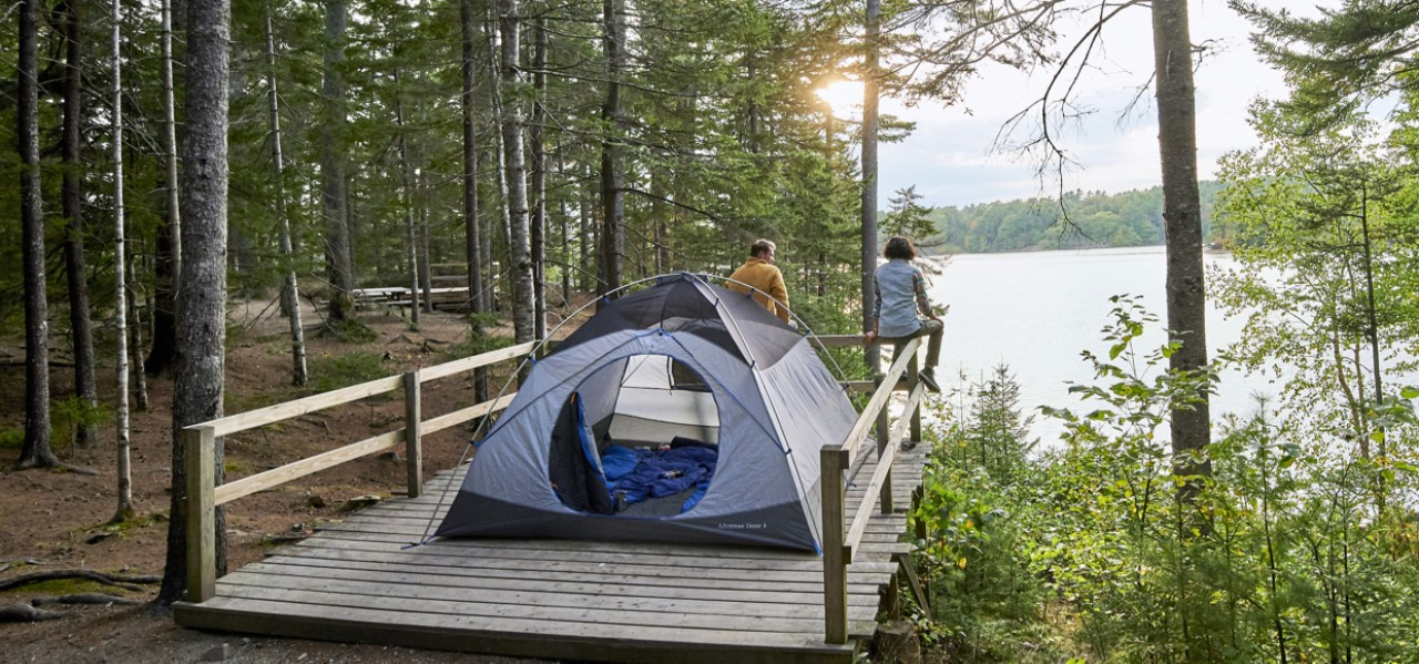 Image of a tent on a platform overlooking a lake.