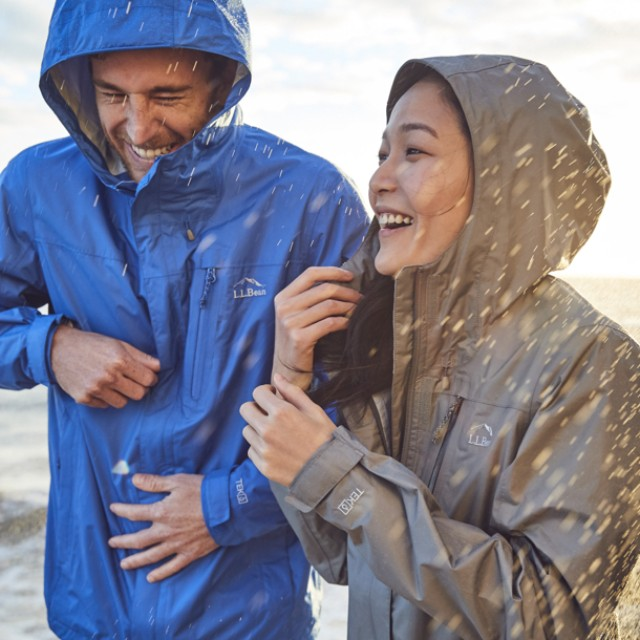 A man and a woman wearing rain jackets with hoods up, walk arm-in-arm in the rain.