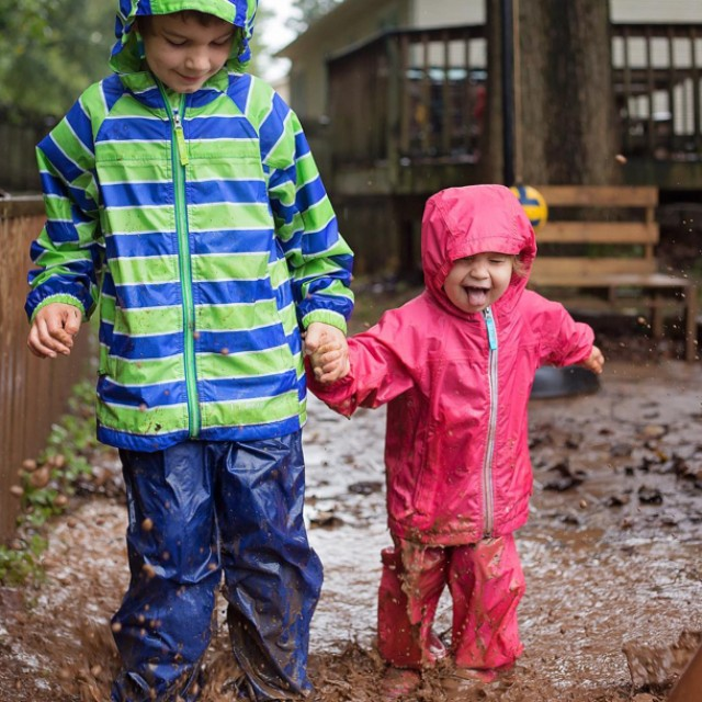 2 kids in rain jackets and pants walking through a mud puddle in the rain.