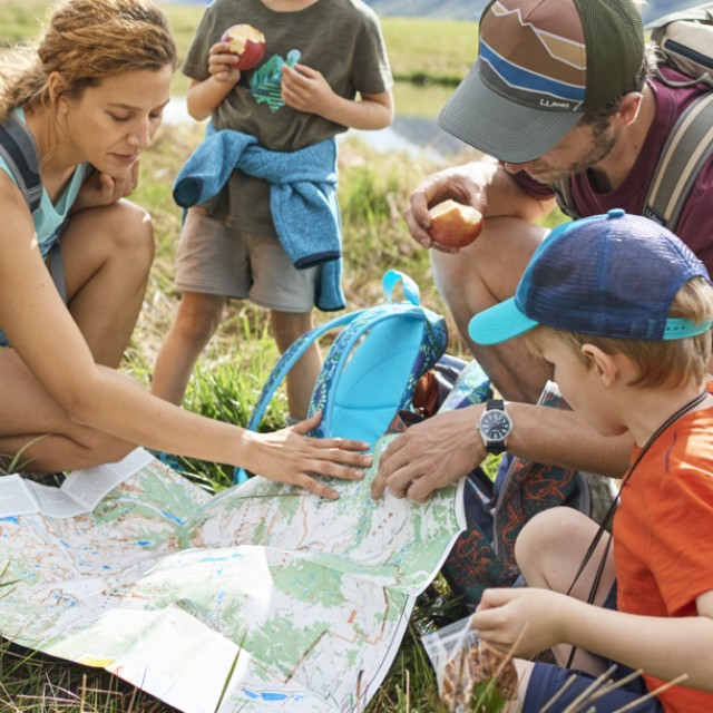 A family of 4 stops along the trail to have a snack and look at a map.