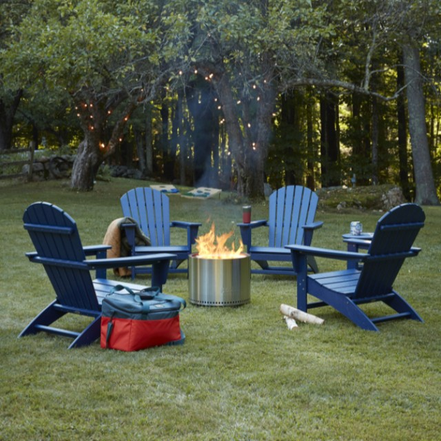 4 blue adirondack chairs in a back yard around a firepit.