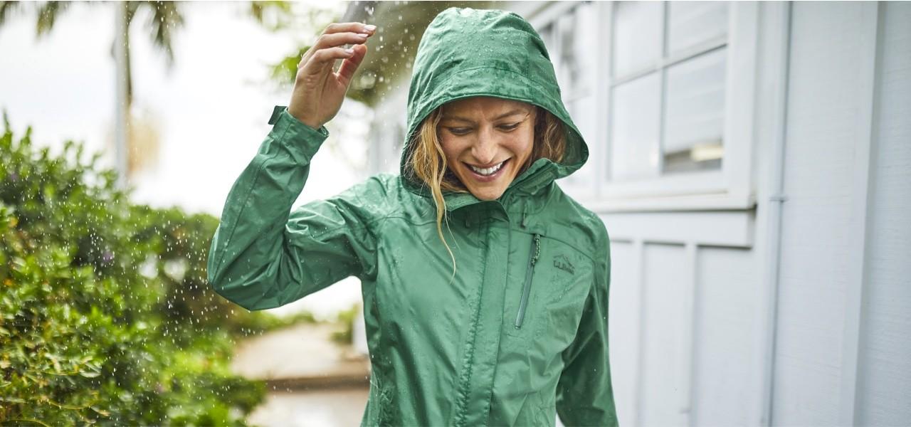 Smiling woman walking in the rain.