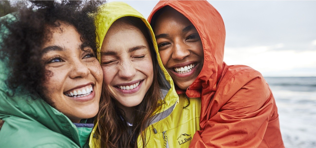Close-up of 3 friends hugging and smiling in the rain.