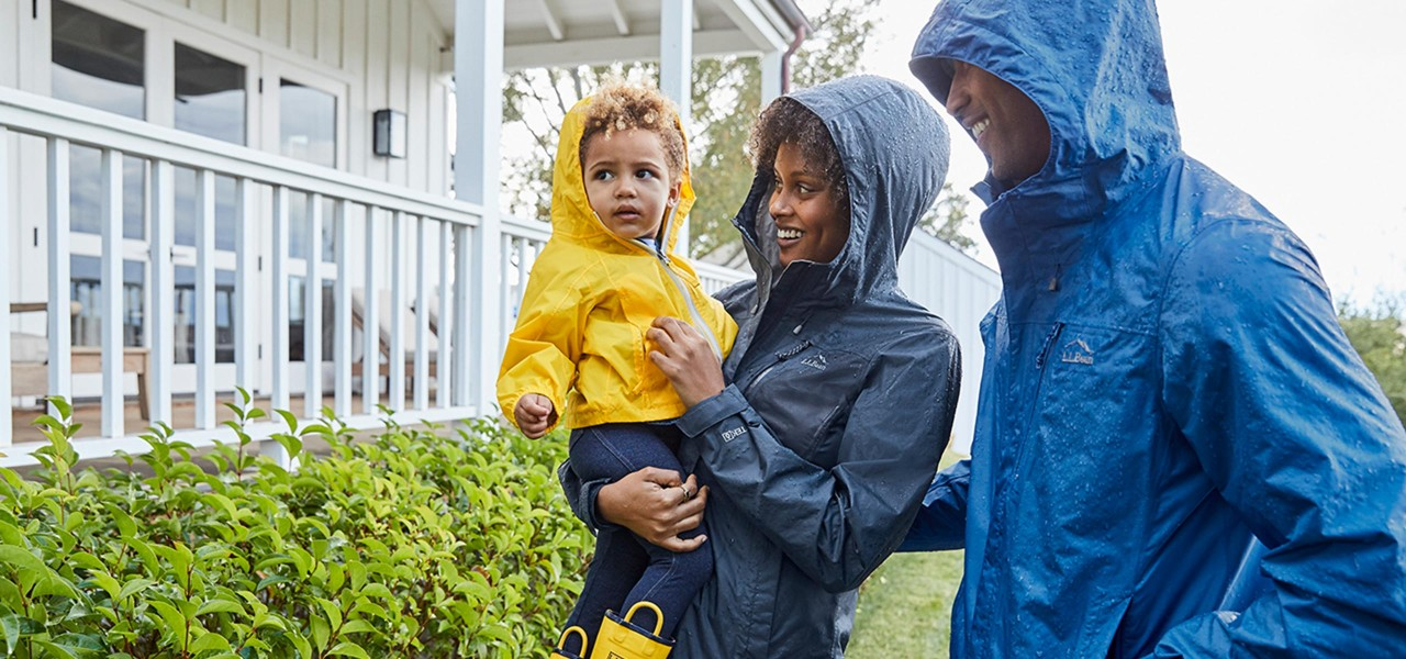 Family standing in the rain smiling.