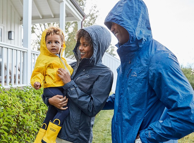 Mom holding toddler with Dad outside in the rain.