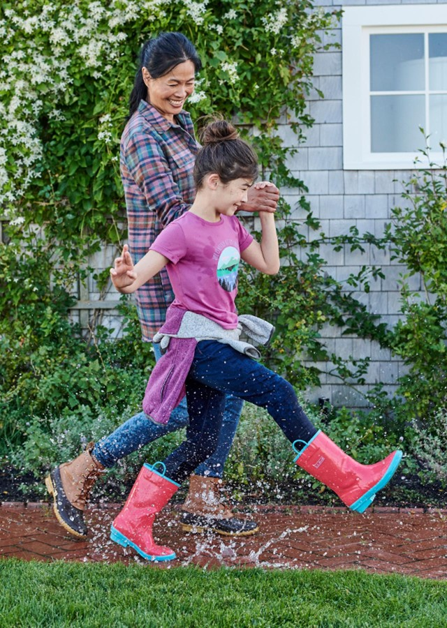 mother and daughter stomping in rain puddles