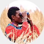 Isaiah Scott sitting in a grassy field looking through binoculars.