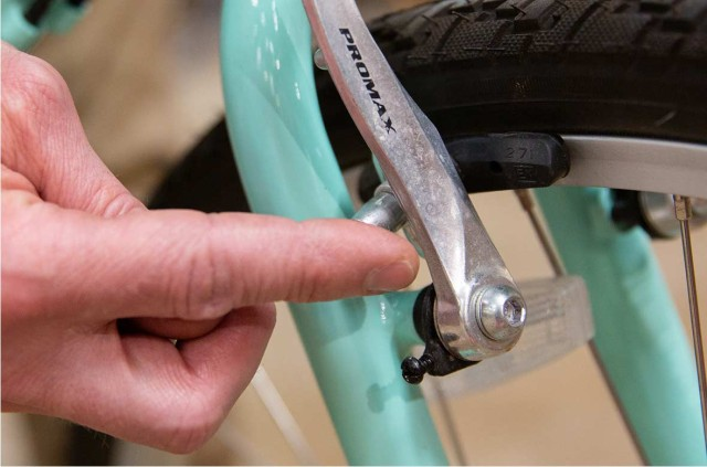Close-up of a hand making an adjustment to bike breaks.