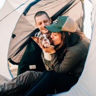 A woman kissing her dog while sitting in a tent.