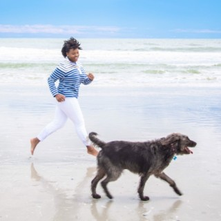 A woman running on the beach with her dog.