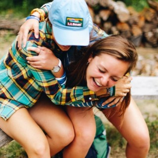 Two friends hugging and laughing.