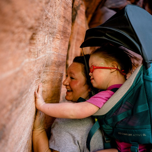 Melody Forsyth and daugther Ruby touching a rock wall on a hike.