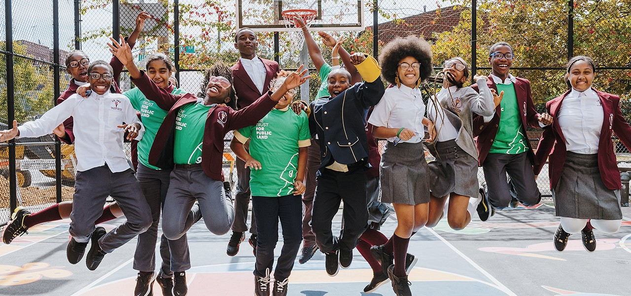 A group of teenagers in school uniforms smiling and jumping