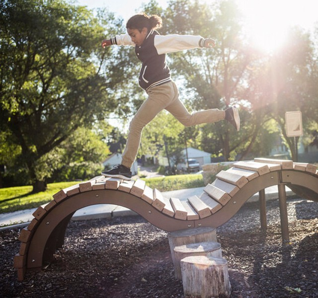 Young girl leaping across a curvy playground structure.