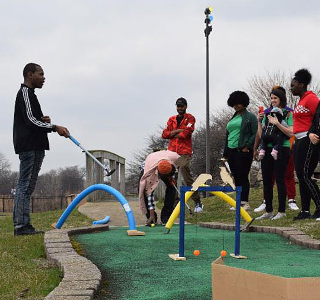 People playing miniature golf.
