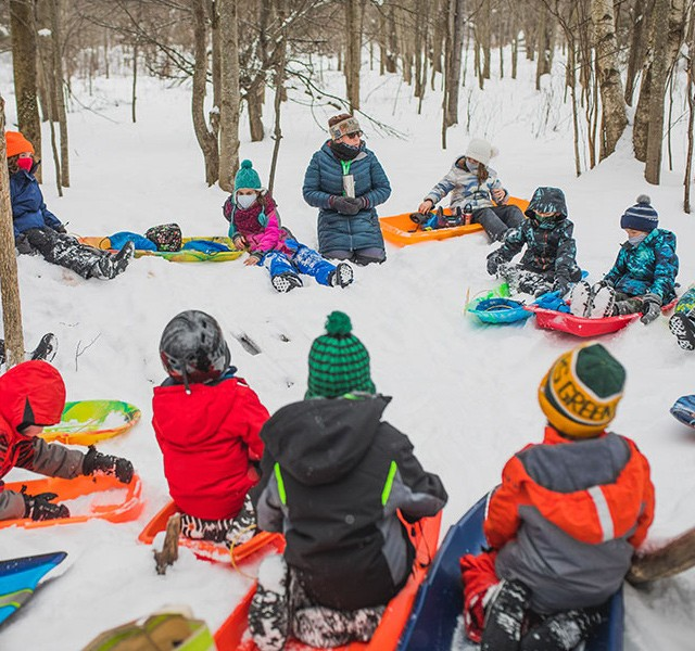 Students and teacher outside in winter, sitting on sleds in a circle.