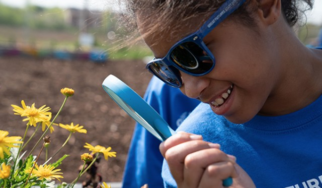 Girl looking a flower with magnifying glass