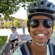 Photo of a woman smiling and riding her bike.