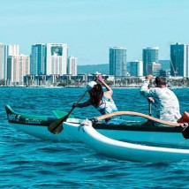 Photo of people paddling with a city view in the background.