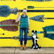 A woman standing with her dog in front of a wall mural.