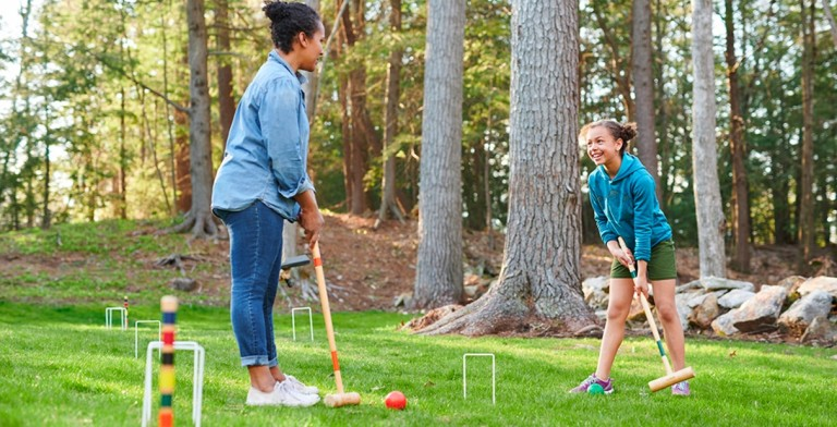 A woman and her daughter playing yard games.